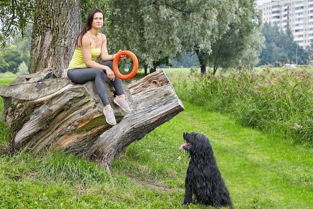 검은 briard와 젊은 여자는 낮에 강아지 산책하는 동안 공공 공원에서 장난감을 가지고 놀고 있습니다.