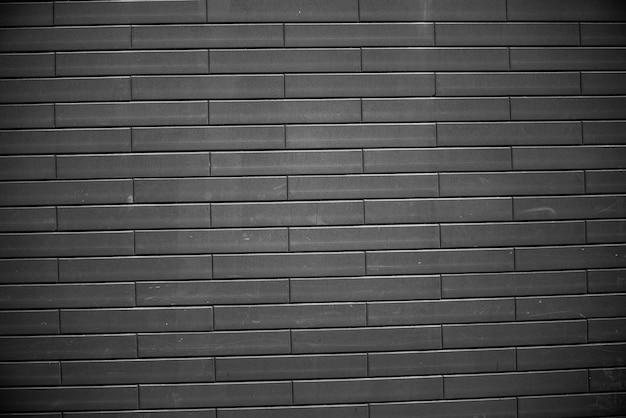 黒レンガの壁。アーバンブラックレンガ壁テクスチャ石積みの背景。