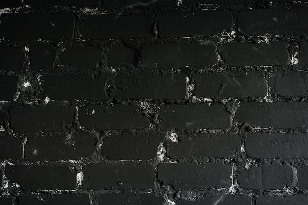 Черная кирпичная стена с трещинами и царапинами