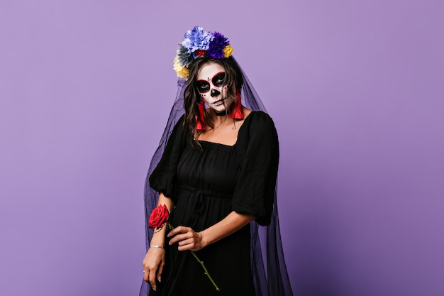 Black bride holding red rose. portrait of model with frightening makeup on halloween.