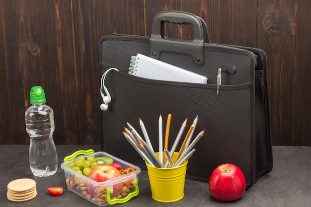 Black briefcase with phone and earphones, bottle of water, lunchbox with fruits and pencils