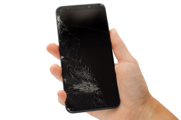 白いひびの入ったタッチスクリーンに手で黒い壊れた携帯電話