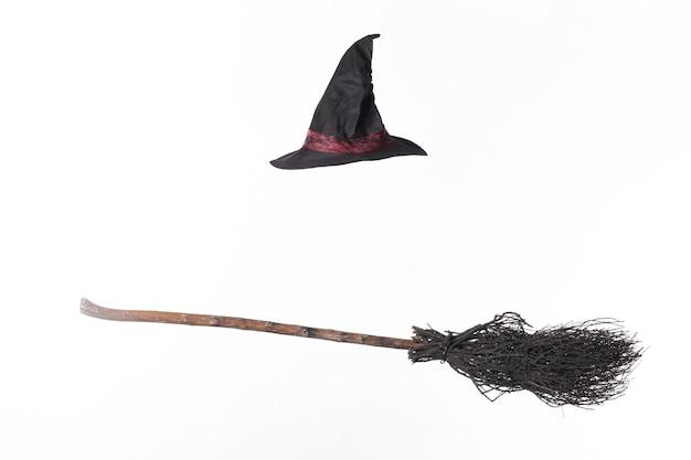 Черная метла и шляпа ведьмы на белом фоне