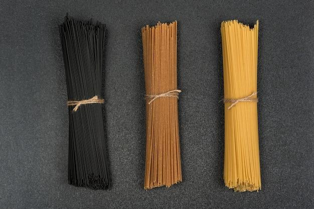 Черные, коричневые и желтые спагетти на сером пространстве. итальянская сухая паста. спагетти космическое.