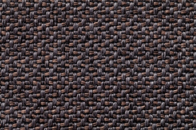 Black and brown vintage fabric with woven texture closeup. textile macro background