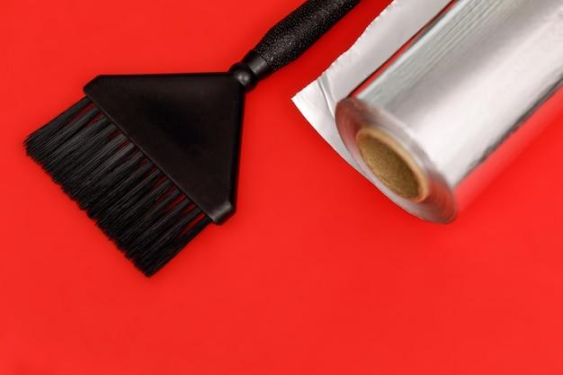 헤어 컬러링을위한 블랙 브러시와 호일 롤. 빨간색 배경입니다.