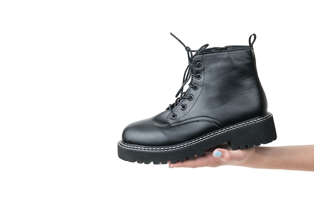 Black brutal women's shoe in a woman's hand isolated on a white surface