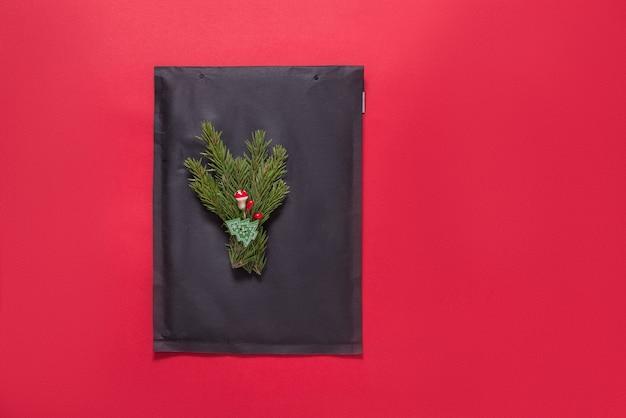 赤のクリスマスツリーの飾りで飾られた黒い泡の封筒
