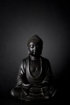 黒の背景と黒の仏像