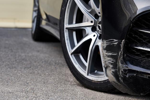 Черный бампер автомобиля поцарапан с глубоким повреждением краски.