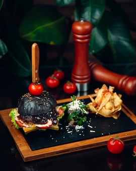 Black burger filled with barbecue sauce and with knife inside