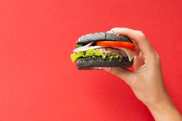 Black burger held in front of red background
