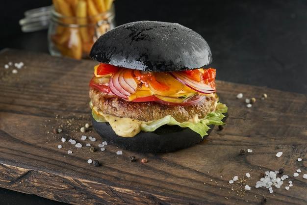 검은 바탕에 소박한 나무 보드에 검은 햄버거.