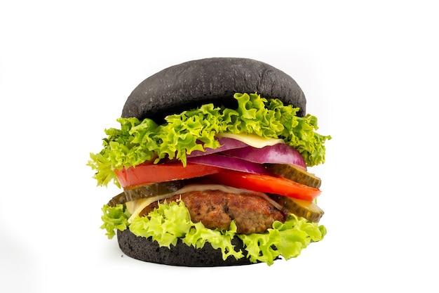 Черный бургер с говядиной, мясом, сыром, салатом, луком, изолированными помидорами