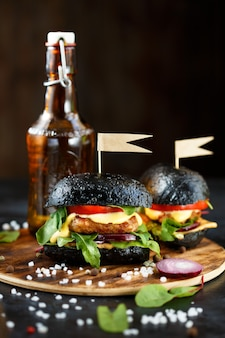 Black burger with cutlet, greens, cheese, onions and tomatoes and a bottle of beer on wooden plate