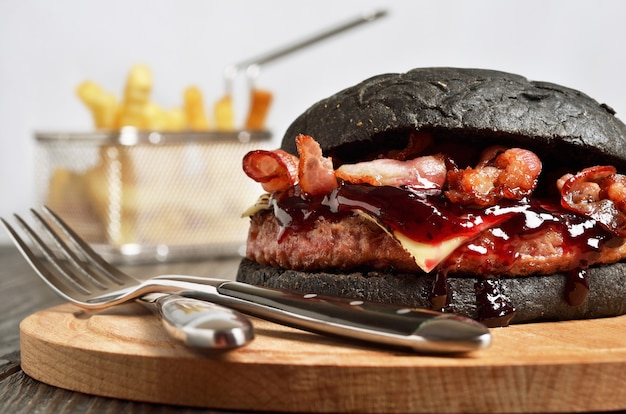 Black burger with french fries on background