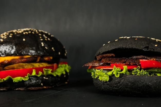 Vista laterale del formaggio del cetriolo del pomodoro della lattuga del manzo degli hamburger neri