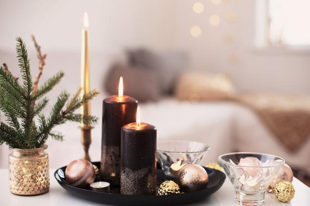 Черные горящие свечи с елочными шарами в белом интерьере