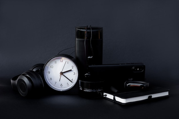 Black business accessories. stationery. watch notebook mobile headphones pen.