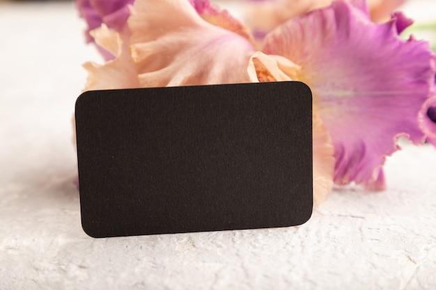 Черная визитная карточка с фиолетовыми цветами ириса на белом фоне бетона. вид сбоку, копировать пространство