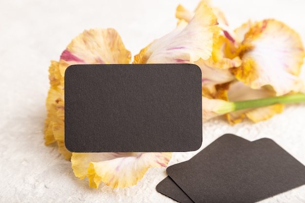 Черная визитная карточка с желтыми цветами ириса на белом фоне бетона. вид сбоку, копировать пространство