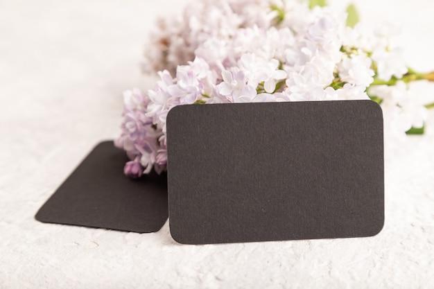 Черная визитная карточка с сиреневыми цветами на сером фоне бетона. вид сбоку, копия пространства,