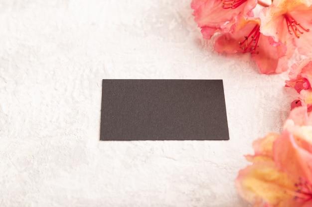 Черная визитная карточка с розовыми цветами азалии на сером фоне бетона. вид сбоку, копировать пространство