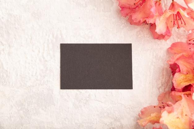 Черная визитная карточка с розовыми цветами азалии на сером фоне бетона. вид сверху, копировать пространство