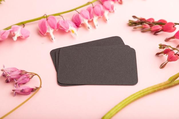 Черная визитная карточка с розовой дицентрой, цветами разбитого сердца на розовом пастельном фоне. вид сбоку