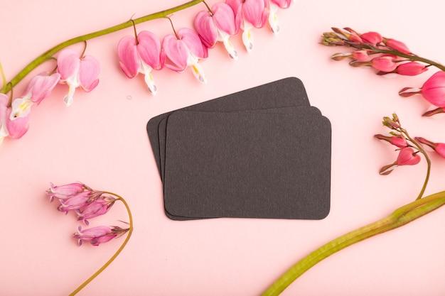 Черная визитная карточка с розовой дицентрой, цветами разбитого сердца на розовом пастельном фоне. вид сверху