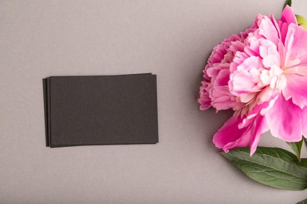Черная визитная карточка с розовыми цветами пиона на сером пастельном фоне. вид сверху, плоская планировка,