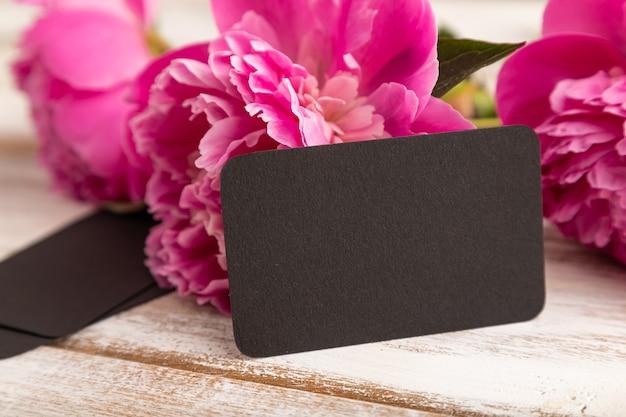 Черная визитная карточка с розовыми цветами пиона на белом деревянном фоне. вид сбоку, копия пространства,