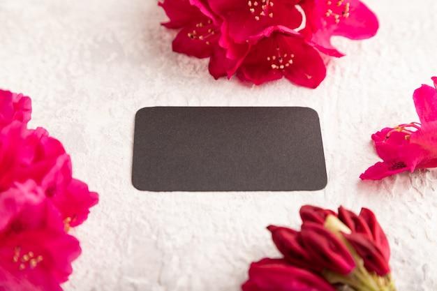 Черная визитная карточка с фиолетовыми цветами азалии на сером фоне бетона. вид сбоку, копировать пространство