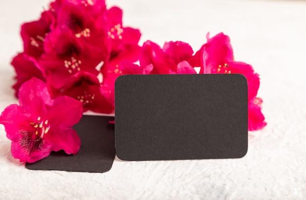 灰色のコンクリートの背景に紫のツツジの花と黒の名刺。側面図、コピースペース