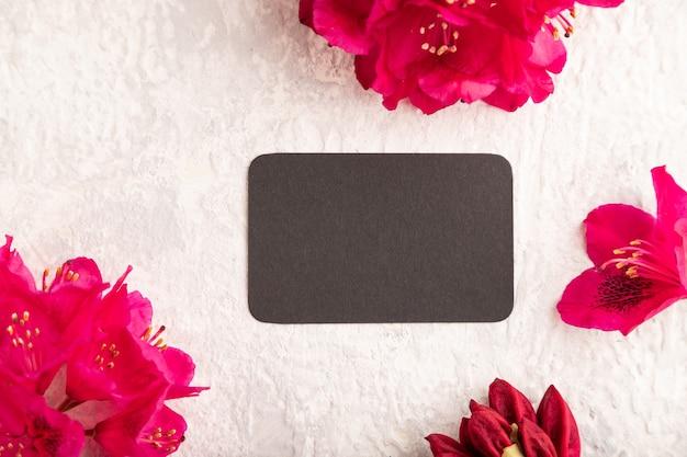 Черная визитная карточка с фиолетовыми цветами азалии на сером фоне бетона. вид сверху, плоская планировка