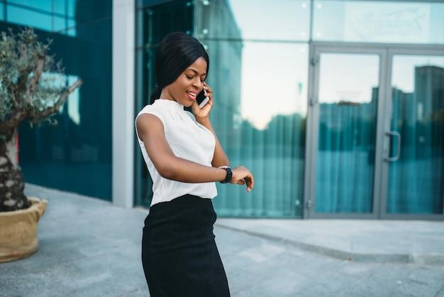 검은 비즈니스 아가씨 휴대 전화로 얘기 하 고 사무실 건물 앞 시계 시간에 보인다.