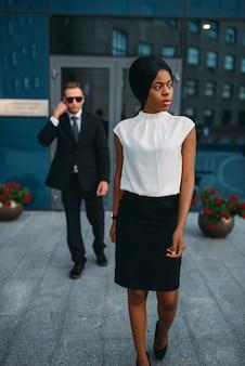 スーツとサングラスで黒のビジネス女性ボディーガード