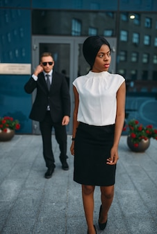 Black business woman bodyguard in suit and sunglasses