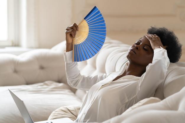 手を振るファンを使用して自宅の居間に座って熱射病に苦しんでいる黒人ビジネスウーマン