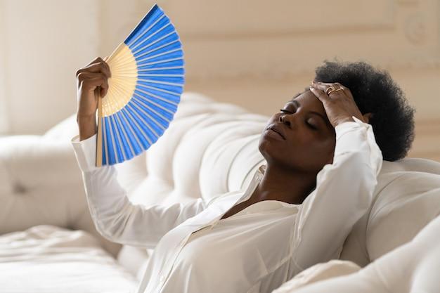 手を振るファンを使用して自宅のリビングルームに座って熱射病に苦しんでいる黒人ビジネスウーマン
