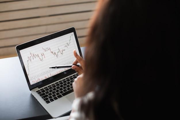데이터 주식 시장 외환 거래 그래프 증권 거래소 거래 온라인 금융 투자 개념을 분석하기 위해 노트북을 사용하는 검은 비즈니스 여자를 닫습니다