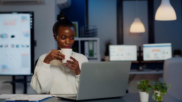 무선 헤드폰으로 커피를 마시는 흑인 여성 사업가는 노트북 앞에 있는 창업 사무실에서 초과 근무를 하는 화상 회의를 하는 동안 커피를 마시고 있습니다. 자정에 가상 회의에서 대화를 사용하는 프리랜서