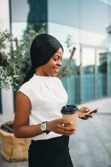 골 판지 커피 컵 블랙 비즈니스 우먼 사무실 건물에 대 한 휴대 전화를 사용