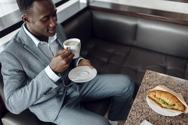 Черный бизнесмен обедает в офисном кафе
