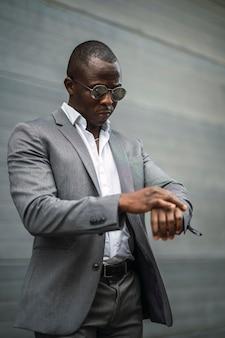 時計を見てサングラスとスーツを着た黒人実業家