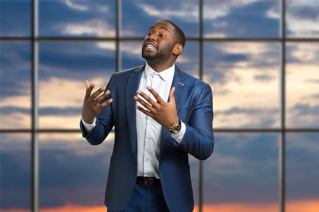 情熱的に話す黒人実業家。フォーマルなスタイルのアメリカ人男性が会議でジェスチャーで話す