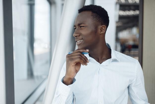 黒人実業家がオフィスビルでポーズをとる。成功したビジネスパーソン、フォーマルウェアの黒人男性