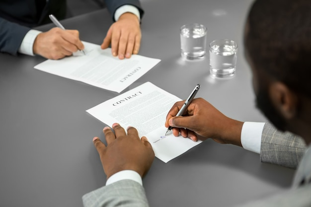 Black businessman signs a contract. welcome to the company. chief employs manager. a successful candidate.