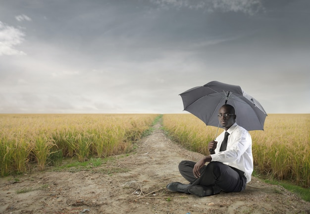 Black businessman sitting outdoor with an umbrella