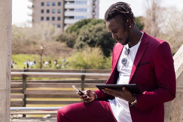 도시에서 야외에서 태블릿과 스마트폰을 사용하는 흑인 사업가